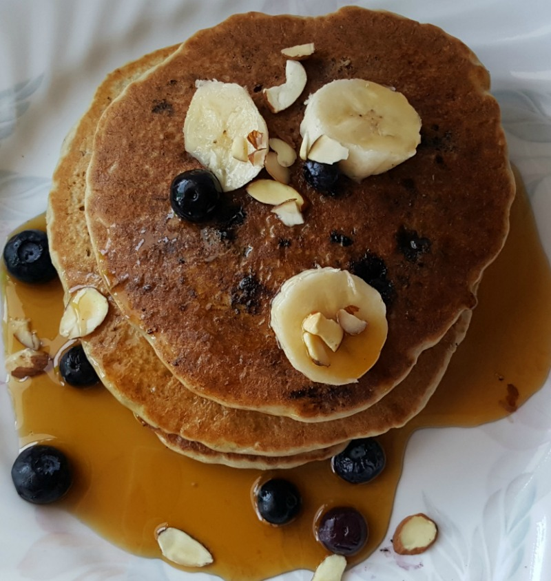 These banana, blueberry, almond pancakes have an extra boost of plant based protein and probiotics from Bob's Red Mill Nutritional Booster Protein Powder. They are vegan, gluten-free, with no extra oil or sugar, and they're delicious!